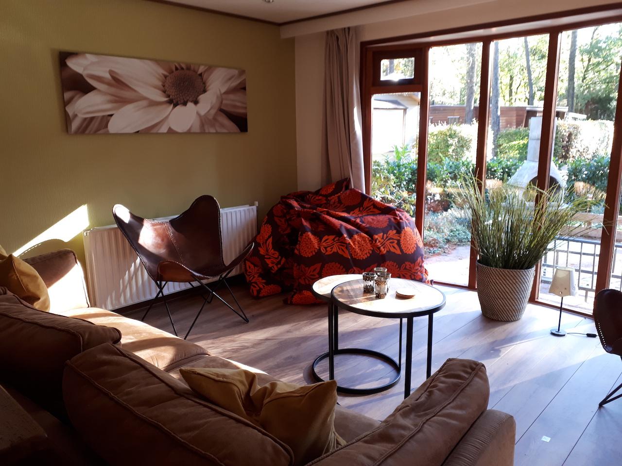 Zonnige woonkamer met openslaande deuren naar veranda